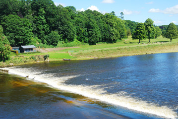 River Tweed weir, meadow and fishing hut near Coldstream