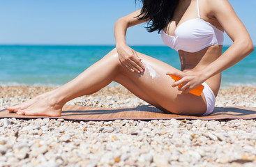 woman apply sunscreen lotion on hip legs