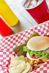 Loaded cheeseburger with ice tea at a picnic