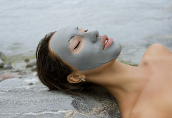 Woman with blue clay facial mask in beauty spa