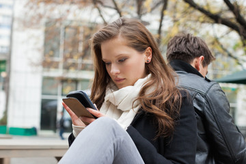 Woman Using Mobile Phone With Boyfriend In Background