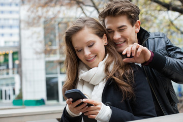 Couple In Winter Jackets Using Mobile Phone