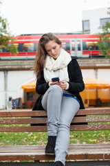Woman Using Cell Phone On Park Bench
