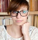 Frau mit Nerdbrille in Bibliothek