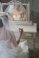 Happy bride looking at mirror