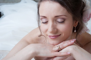 Happy smiling bride dreams in white dress in bedroom