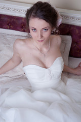 Happy smiling bride dreams in white dress lie in bedroom