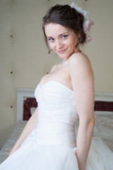 Happy smiling bride dreams in white dress