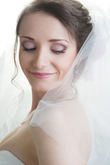 Portrait of young smiling happy bride looking down