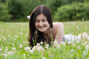 Beautiful happy Girl lying on grass field in summer park