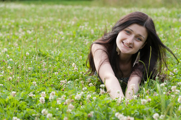 Beautiful happy smiling Girl lying on grass field in summer park