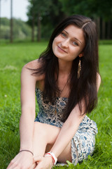 Young pretty smiling girl relaxing on grass in Park