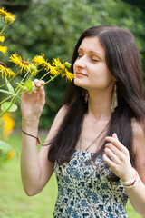 young woman close-up smelling yellow flower