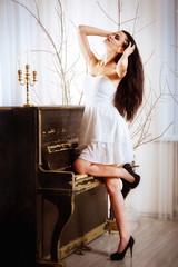 Девушка стоит у пианино