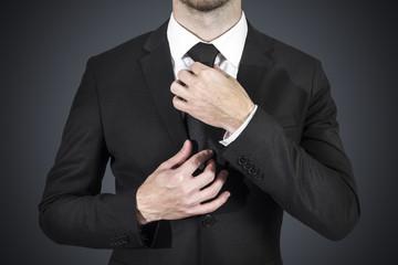 businessman wearing black suit correcting his tie