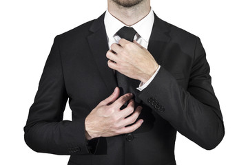 businessman wearing black suit correcting his tie