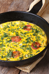 Frittata with green onions, tomatoes in a pan closeup