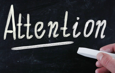 attention handwritten with chalk on a blackboard