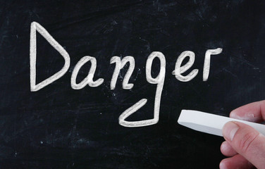 danger handwritten with chalk on a blackboard