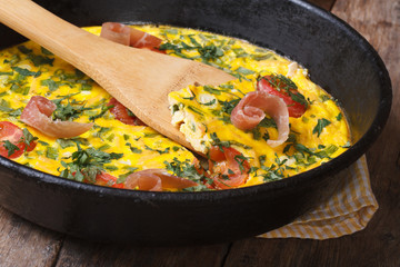 Frittata with tomato, ham and herbs  in the pan with a spatula