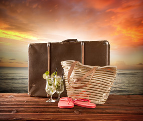 Old suitcase with accessories on beach in dusk