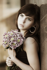 Sad young woman with a flowers at the wall