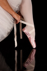 Ballerina put on slippers to prepare for performance with reflec