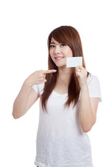 Asian girl point to a white card and smile