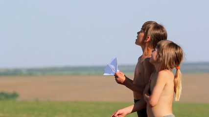 Children playing with a paper airplane.