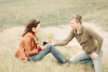 Young man offering yellow wildflowers to a girl