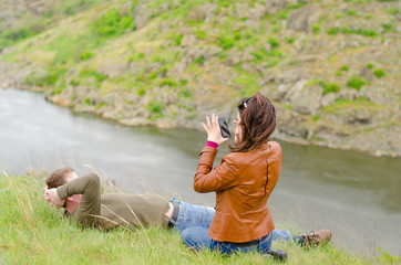 Young woman photographing a man on a cliff top