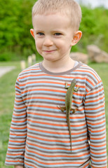 Cute little boy with a live lizard on his shirt