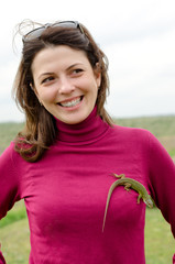 Beautiful happy woman with a lizard on her breast