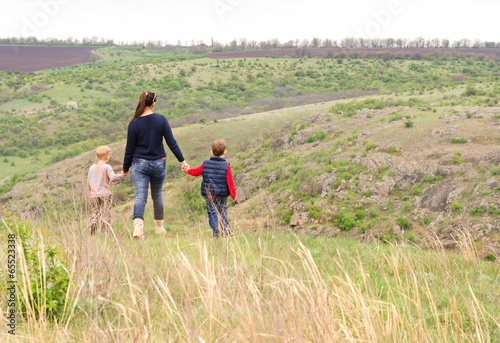Mother walking with two boys in the countryside