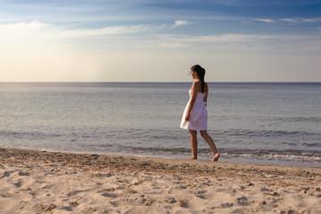 Nachdenkliche Frau geht am Strand
