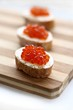 Red caviar in spoon on a baguette