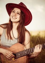 smiling woman in hat with guitar