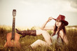 young cowgirl in red hat at spring meadow with guitar