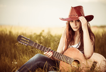 young stylish cowgirl with guitar at spring meadow