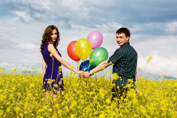 Happy couple with balloons on the yellow field