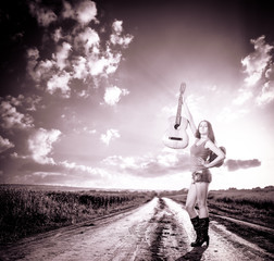 woman with guitar at rural road