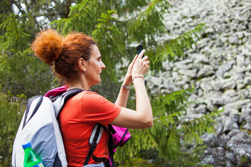 Woman hiker taking photos with cellphone