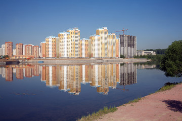 Many block of flats over river and clear blue sky