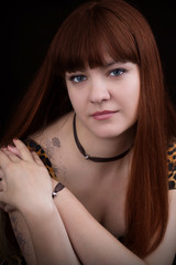 Portrait of red-haired girl with tattoo