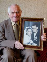 80 plus year old senior man holding his wedding photograph.