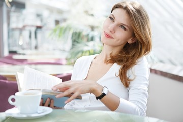 photo of beautiful woman sitting in a café with a book