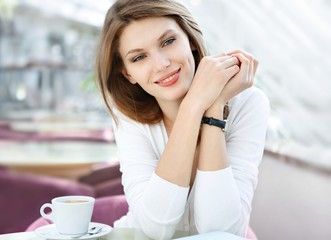 photo of beautiful woman sitting in a coffee house