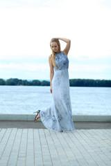 Beautiful young woman in blue long dress