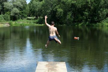 one man jumping into lake