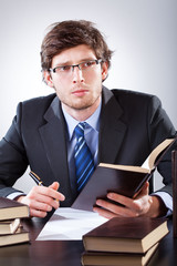 Businessman reading a book and writing